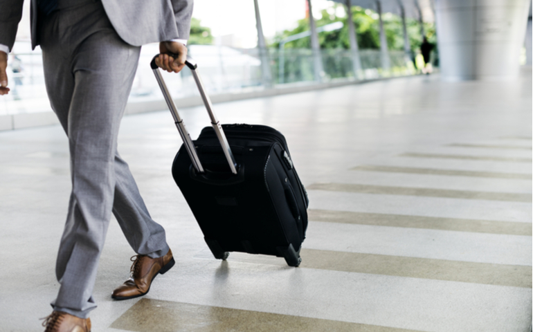 Businessman in suit walking through airport with luggage