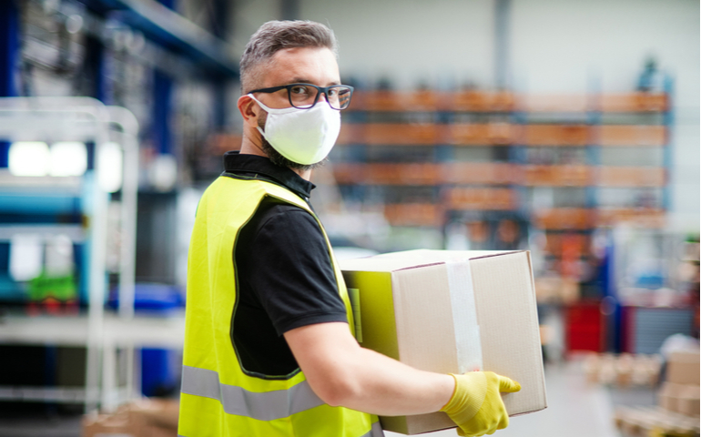 Warehouse worker wearing protective mask and carrying cardboard box